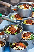 A stack of saucepans with vegetables and spicy sauce