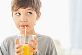 A little boy drinking orange juice from a glass with a straw