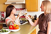 Two women raising a toast with wine glasses in kitchen
