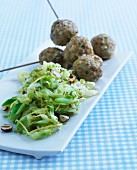 Cabbage salad with hazelnuts served with meatballs on sticks