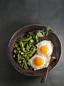 Fried eggs with a pea salad