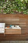 Ablagefläche neben Aussengrill an modernem Holzzaun einer Terrasse befestigt