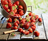 Fresh strawberries in a colander and on a wooden table, some sliced