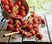 Frische Erdbeeren im Fussseiher und auf Holztisch, teilweise geschnitten