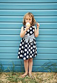 Little girl with large ice-cream standing against blue wall