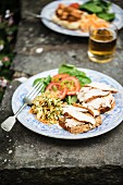 Slices of bread topped with chicken and served with salad