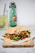 A pulled pork sandwich with basil on a chopping board