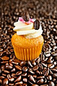 A mini vanilla cupcake on coffee beans