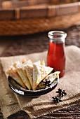 Dreieckiges Blätterteiggebäck mit Nüssen, Gewürzen und Rosensirup