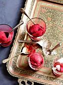 Raspberry sorbet in dessert glasses on a tray