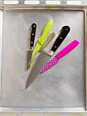 Various kitchen knives on a baking tray
