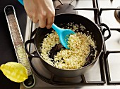 Risotto rice being fried in a pot with lemon zest