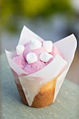 A vanilla cupcake decorated with raspberry cream and mini marshmallows