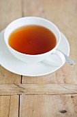 A cup of black tea on a wooden table