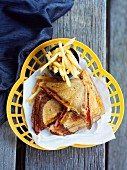 Toasted ham and cheese sandwiches with fried in a plastic basket