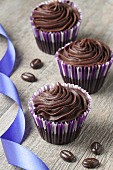 Three chocolate ganache cupcakes with chocolate beans and a ribbon