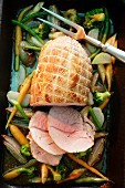 Roasted pork roulade on a bed of vegetables in a roasting tin with three slices cut