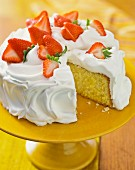 Sponge cake topped with meringue and strawberries, sliced