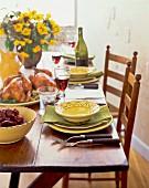 Gedeckter Tisch mit Hähnchen, Salat und Wein