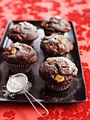 Chocolate muffins with pecan nuts and icing sugar