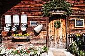 Almhütte mit Milchkannen und Blumenschmuck (Österreich)