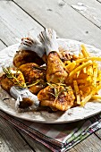 A plate of chicken drumsticks and fries
