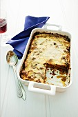 Moussaka in a baking dish with a slice cut out