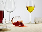 A glass of red wine falling over