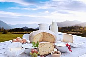 An arrangement of dairy products and eggs against a beautiful mountain skyline