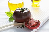 A black tomato on a wooden spoon