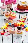 A colourful birthday buffet featuring cake and cupcakes