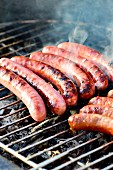 Chipolata sausages on a smoking barbecue
