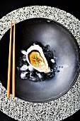 Auster mit Ingwer, Miso und Chili auf Eiswürfeln in schwarzer Schale mit Stäbchen (Japan)