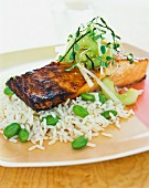 Salmon fillet on a bed of rice with broad beans