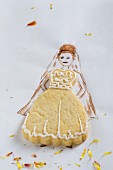 A wedding dress-shaped biscuit on a piece of paper with the bride drawn on