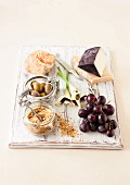 An arrangement of cheese, grapes, bread and Gomasio