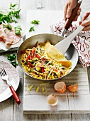 Omelette with ham, sweetcorn and cheese in a pan