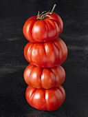 A stack of four beefsteak tomatoes against a black background