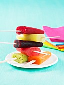 Colourful homemade fruit ice lollies stacked on a plate