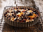 Apricot and blueberry clafoutis in a tart tin on a wire rack