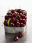 Freshly washed cherries in a metal container