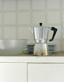 An espresso maker, a stack of plates and a glass bowl