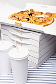 A stack of pizza boxes next to cups of soda