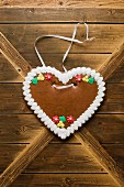 A gingerbread heart hanging on a wooden wall