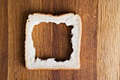 The middle removed from a slice of bread