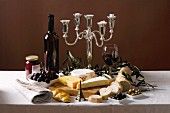 Various types of cheese with baguette, olives, grapes and red wine from France