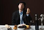Typischer Franzose mit Käseplatte, Trauben und Rotwein