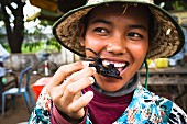 A woman eating fried a tarantula, Cambodia