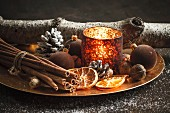Christmas decoration with a tea light, Christmas baubles, cinnamon sticks, dried orange slices and walnuts on a plate