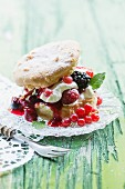 A profiterole with cream and berries on a green table